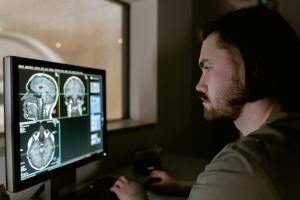 radiologist reviewing brain scans on computer